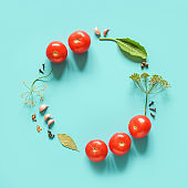Pickled tomatoes. Circle frame made ingredients for marinated tomatoes on blue background. Concept culinary recipe preservation of vegetables in harvest season. Creative flat lay Top view Copy space