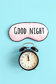 Good night text on pink sleep mask for eyes and black alarm clock on blue background. It 's midnight Top view. Concept eye protection from light for good sleep and melatonin production