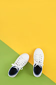 White sports shoes, sneakers with shoelaces on a green and yellow background. Sport lifestyle concept Top view Flat lay