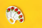 Red ripe strawberries on an artistic palette on yellow background with copy space. Creative concept summer colors paint. Top view Flat lay Template for design postcard invitation