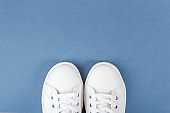 White sports shoes, sneakers with shoelaces on blue background. Sport lifestyle concept Top view Flat lay Copy space