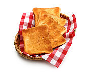 Wicker plate with slices of toasted bread on white background