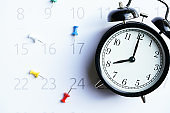 close up of alarm clock and calendar on the table, planning for business meeting or travel planning concept