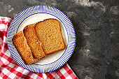 Plate with tasty toasted bread on grunge background