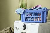 Basket with dirty laundry on washing machine