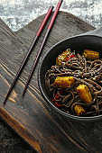 Bowl with tasty soba noodles, corn cobs and chili on wooden board