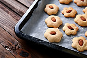 Baking sheet with tasty cookies on wooden table