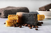 Soap bar with coffee beans and honeycombs on color table
