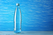 Bottle of clean water on table against color background