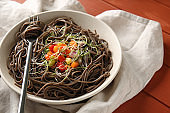 Bowl with tasty soba noodles and vegetables on table