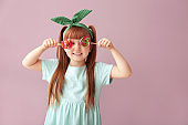 Cute little girl with lollipops on color background