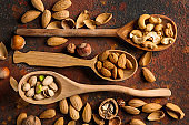 Spoons with different tasty nuts on color background