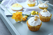 Tasty Easter cupcakes on tray, closeup