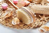 Massage brush with sea shells on wicker tray, closeup