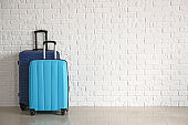 Packed suitcases near white brick wall