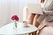Young woman using laptop near table with cup of coffee at home