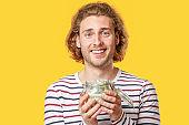 Handsome man holding jar with money on color background