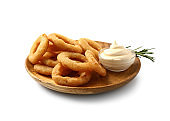 Plate with tasty onion rings and sauce on white background