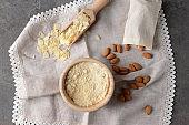 Bowl with tasty almond flour on grey table
