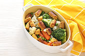 Casserole with tasty corn cobs and vegetables on white table