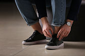 Fashionable young man putting on shoes, closeup