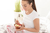 Beautiful young woman eating tasty oatmeal for breakfast in bedroom