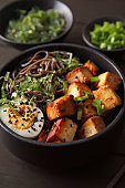 Bowl with tasty fried tofu cheese and soba noodles on table