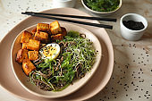 Plate with tasty fried tofu cheese and soba noodles on table