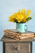 Cup with beautiful yellow flowers and old book on table against color background