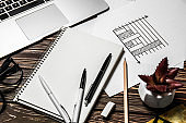 Notebook with stationery, graph and laptop on wooden table. Concept of business planning