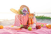 Wicker basket with tasty food and drink for romantic picnic near river
