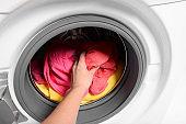 Woman putting dirty laundry in washing machine, closeup