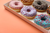 Sweet tasty donuts in box on color background