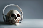 Human skull with headphones on grey background