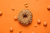 Sweet tasty donut and candies on color background