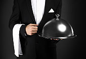 Handsome waiter with tray and cloche on dark background