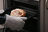 Woman taking baking tray with homemade bread out of oven