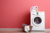 Modern washing machine and laundry near color wall