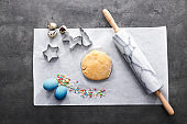 Composition with dough for Easter cookies on grey table