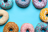 Frame made of sweet tasty donuts on color background