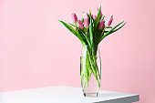 Vase with bouquet of beautiful tulips on table