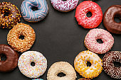 Frame made of sweet tasty donuts on dark background
