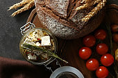 Glass jar with marinated cheese and tasty bread on wooden board