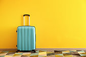 Packed suitcase near color wall