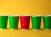 Red cup among green ones on color background. Concept of uniqueness