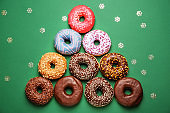 Composition with sweet tasty donuts on color background