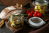 Glass jars with marinated cheese and tasty bread on wooden board