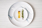 Plates with bottle of rosemary oil on white table