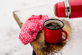 Red mug with hot coffee or tea drink on snow in winter