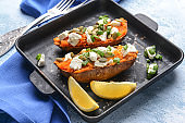 Baked sweet potato with cheese and arugula in frying pan